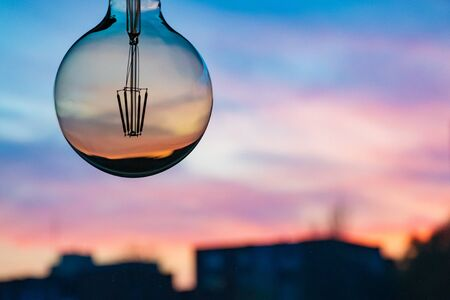 Beautiful defocused sunset in a light bulb. Sunset or sunrise background. Electricity concept. Earth hour. Energy consumption and environmental conservation, energy saving Banco de Imagens