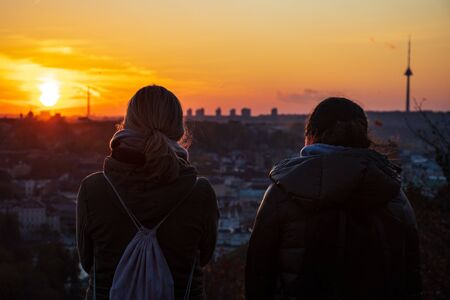 Two friends looking at the sunset in Vilnius, panorama with buildings and the TV tower Reklamní fotografie