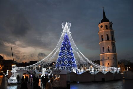 Beautiful Christmas tree decorated with white and blue lights for Christmas 2019 and New Year 2020, market and celebrations in Vilnius Cathedral square