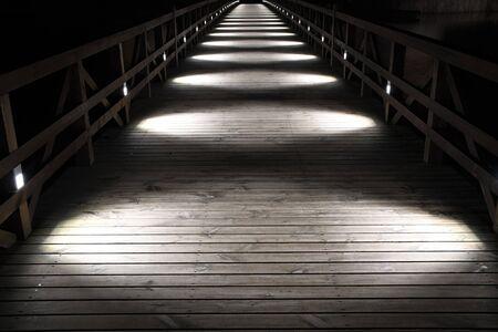 Puente de madera iluminado por luces circulares blancas en la noche, perspectiva