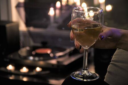 Girl with red nails drinking white wine with vinyl player and candles on background, relaxing and cozy atmosphere