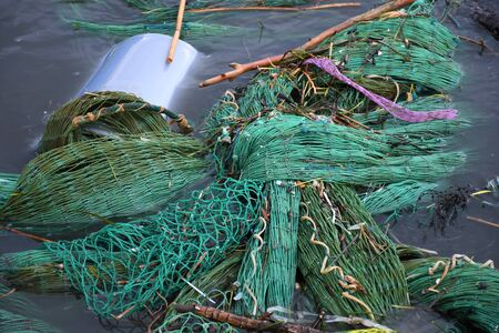 Plastic and microplastic waste and garbage floating in the water with fishing net. Ocean and sea plastic pollution