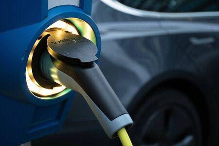 Estación de recarga de vehículos eléctricos, estación de recarga de vehículos eléctricos, punto de recarga eléctrica, punto de recarga, punto de recarga, estación de recarga electrónica ECS con coche al fondo