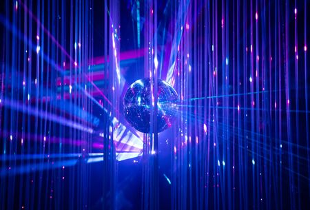Dance floor disco night with a mirror ball symbol of fun and party in a nightclub or dance club with glowing stage lights and reflections, blue, violet, purple
