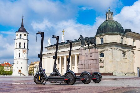 Electric urban transportation, row of electric readies to ride scooter bikes with accumulators in the center of a city