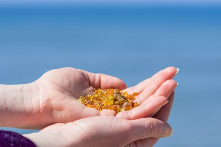 Beautiful pieces of amber in the hand of a girl with blue sky background