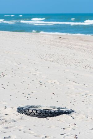 Big black rubber tire left on a sandy beach with blue sea and waves on background, environment pollution concept, vertical