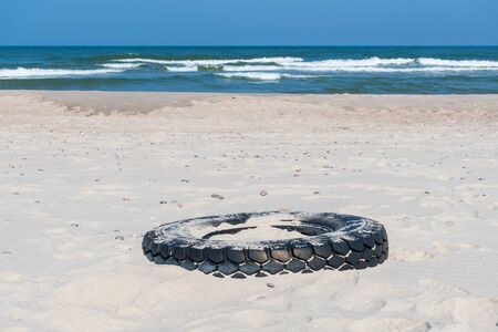 Big black rubber tire left on a sandy beach with blue sea and waves on background, environment pollution concept