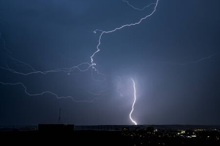 Beautiful night landscape with thunderstorm lightning bolts with rain and stormy sky over the city Foto de archivo