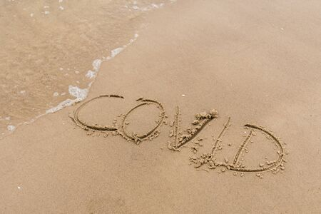 Covid written on the sand of a beach with wave washing, erasing or canceling it during Coronavirus summer, Covid free, STOP Covid, safe beach