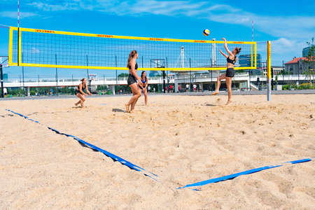 Girls playing beach volleyball in summer in the city