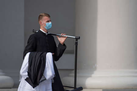 Young priest with protective face mask going to the church to celebrate mass during second wave of Covid or Coronavirus outbreak