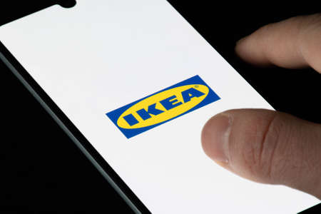 Vilnius, Lithuania - December 10 2020: Ikea app on the smartphone or device, with finger of the user. Ikea decided to stop printing and publishing catalog, catalog or brochure