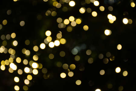 Abstract background yellow bokeh lights and branches of a tree in winter, Christmas or party background, cozy and warm feelings Stock Photo