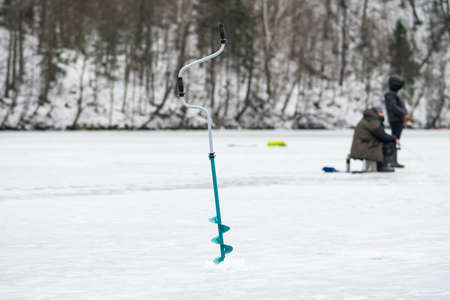 Fishermen fishing on a frozen lake in winter with fishing pole, ice auger and equipment for fishing