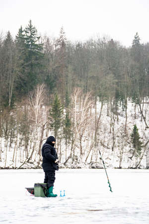 Fisherman fishing on a frozen lake in winter with fishing pole, ice auger and equipment for fishing
