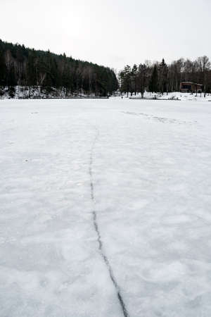 Fracture on the ice on the surface of a frozen lake or river with forest on background, vertical Stock fotó