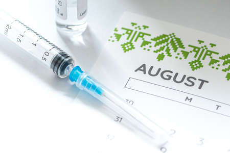 Syringe, vial and calendar with month of August on a white table ready to be used. Covid or Coronavirus vaccine background