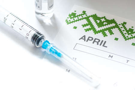 Syringe, vial and calendar with month of April on a white table ready to be used. Covid or Coronavirus vaccine background