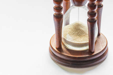 Wooden vintage hourglass close up. Sand passing through the glass bulbs of an hourglass measuring the passing time as it counts down to a deadline or closure on a white empty background