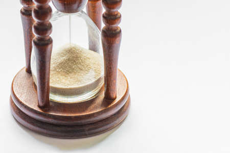 Wooden vintage hourglass close up. Sand passing through the glass bulbs of an hourglass measuring the passing time as it counts down to a deadline or closure on a white empty background on right side