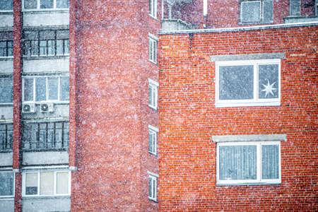 Windows and balconies of soviet blocks buildings with red bricks during big snowfall