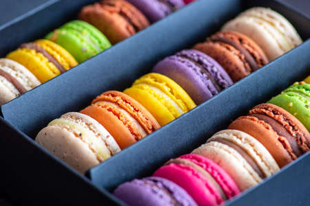 Various colorful macarons or French macaroons in a row in a gift box, sweet meringue-based confection made with egg white, icing sugar, granulated sugar, almond meal, and food coloring, close up
