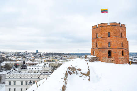 Gediminas Tower or Castle, the remaining part of the Upper Medieval Castle in Vilnius, Lithuania with Lithuanian flag in winter day with snow Sajtókép