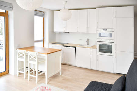 Modern Scandinavian-Style kitchen or living room, minimalist interior design, oven, microwaves and sink with wooden board, table and chairs, white and wooden color, furniture Stock fotó