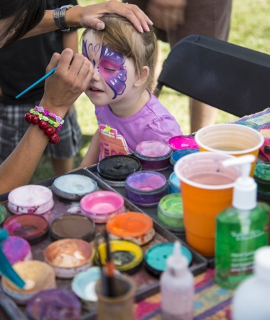 children painting: young girl at festival getting her face painted as a butterfly