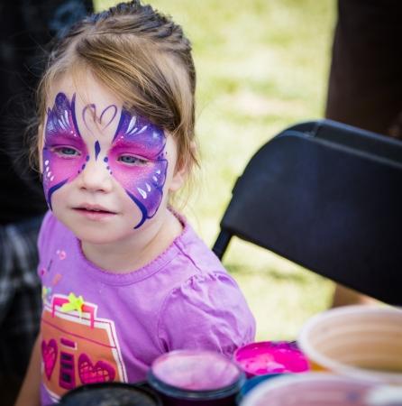 pintura en la cara: Chica joven en el festival de conseguir su rostro pintado como una mariposa