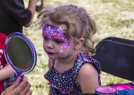 pintura en la cara: Chica joven en el festival con su rostro pintado brillante morados y rosas como una princesa admirándose en el espejo Foto de archivo