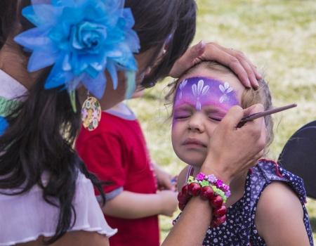pintura en la cara: maquillaje y pintura de cara de las muchachas jóvenes en brillantes morados y rosas como una princesa