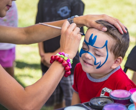 'face painting': young boy at festival getting a batman face painting