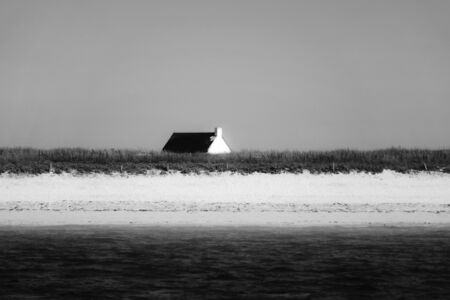 Black and white picture of a beach house above a dune by the sea in a foggy morning. Stockfoto