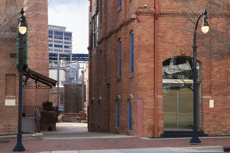 lampost: downtown city street with brick buildings and lampost with view of back alleyway Stock Photo
