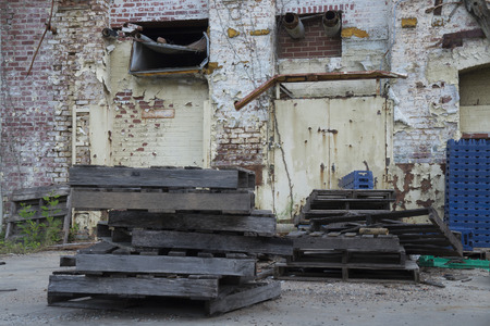 abandoned warehouse: Exterior ruins of an abandoned warehouse with brick paint peeling walls, wooden and plastic crates, pipes, and steel door. Stock Photo