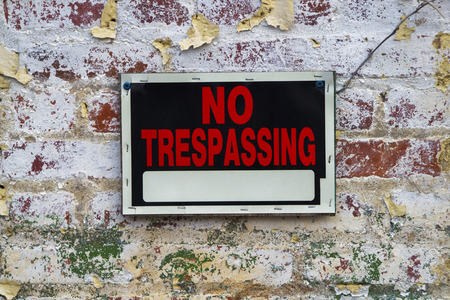 trespassing: Black, white, and red No Trespassing sign on a peeling painted distressed brick wall
