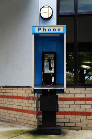 cabina telefonica: Old blue phone booth under light near storefront