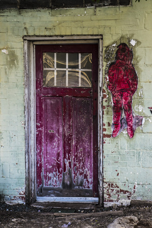 back alley: Red destressed door with red graffiti in back alley