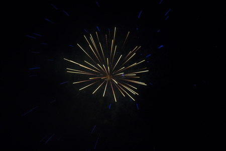 fading: Light colors inner burst with blue outer burst from fireworks on a dark black sky with fading smoke Stock Photo