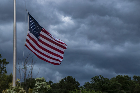 spangled: American flag waving during a storm with storm clouds background and trees