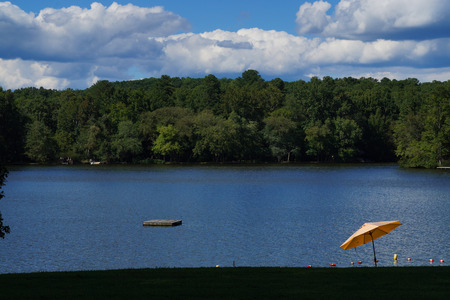 lakeview: Lakeview with trees, cloudy skies and yellow umbrella