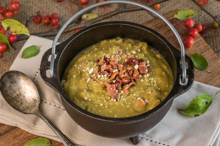 Split Pea Soup in Cauldron on cutting board Stockfoto