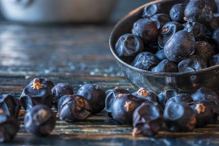 measuring spoon: juniper berries spilled from measuring spoon