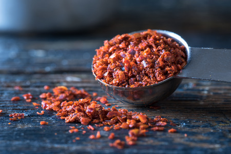 measuring spoon: Aleppo Peppers spilling from measuring spoon