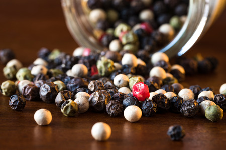 Peppercorns spilled from spice jar