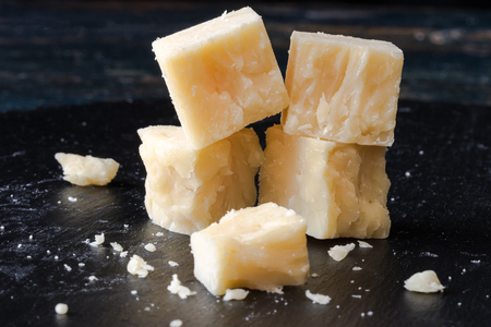 Witte cheddar kaas kubussen op zwarte lei