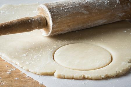 Snijd koekjesdeeg uit met deegroller Stockfoto