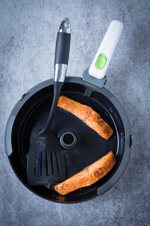 Two cooked filets of salmon in an air fryer with a spatula on a dark, grunge background. Healthy salmon meal. Air fried salmon filet. Stok Fotoğraf